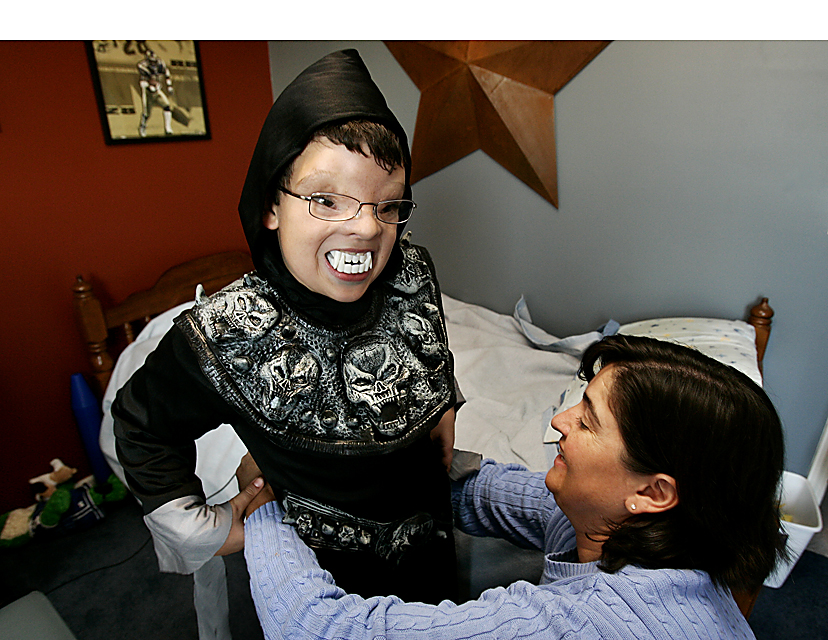 Grant tests his teeth out as his mom, Lora Vacca, helps him get his Halloween costume on.