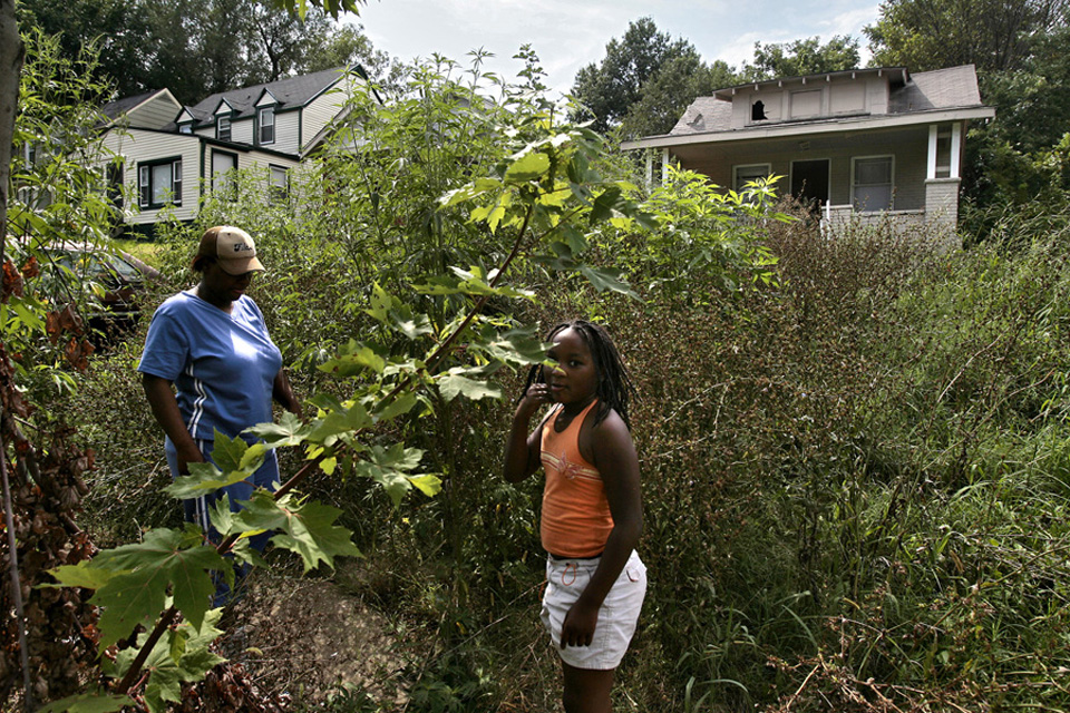 Jackie Stovall, daughter Jaleeah Stovall, 10, and family, have lived in their home in the 5500 block of Olive for three years.  The vacant house next door was surrounded by overgrown weeds for about a year before they were recently cut.  Drugs were sold from the house before it was vacated.