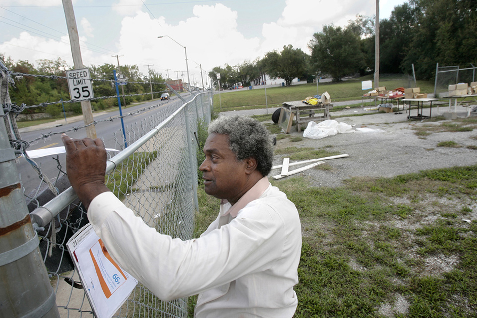 "James Porter gets the mail through the barbed wire surrounding his car lot on Prospect Avenue, which was a once bustling commercial street running through the heart of 64130.  He offers ""free stuff,"" shown in the lot behind him, to passers-by.  Porter estimates that his property has been broken into 30 to 40 times in the last 12 years."