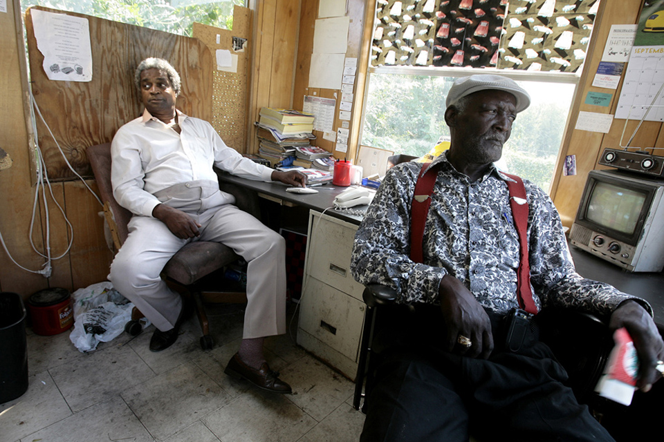 James Porter, left, and friend Rev. James Paden hang out in the office of Porter Investment Corporation.  Porter leaves the board in the window behind him in place permanently now, after so many broken window repairs.