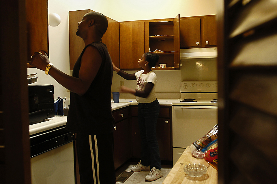 "Amrine and his niece, Rachel ""Shapumpkin"" Hendricks, 11, look in the bare cabinets for some sugar.  After living together for a while, Amrine and his girlfriend, Carmelia Beverly, split up.  When she moved out, he had to start over, buying more food and furnishings for the apartment."