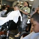 Following a desire to be his own boss, Joey Thomas, center, opened JoeyCuts Barber Salon in July 2008.  He hopes to help out youths in the community with a center.