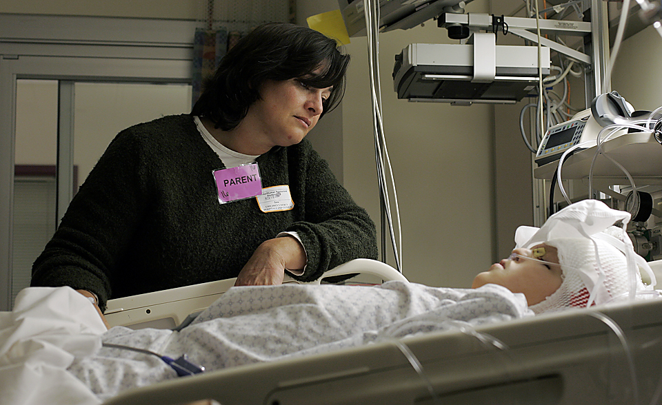 In Grant's room in the intensive care unit, Lora looks at her son.