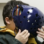 While waiting for Dr. Singhal to examine him, Grant covered his face with the helmet he had to wear when traveling.  Grant said he liked the way the light came through the holes.