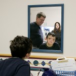 "After the stitches and sponges around his nose bridge were removed, Grant peers at his face.  ""I feel like my old self again,"" he said, as his dad, Brian, and physician assistant Pam Mullin, watch."