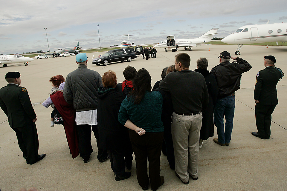 Family and friends watch as the remains of Sgt. Aaron Smith is carried to the hearse. at Kansas City International Airport.