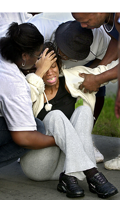 A woman is comforted after she learned that her stepfather had been killed. An employee killed five and himself at the ConAgra plant in Kansas City, Kansas, in July 2004.