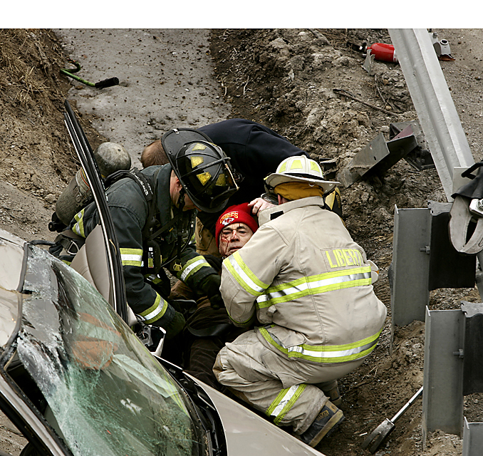 Emergency crews work to move to an ambulance one of the survivors of a four-vehicle accident in Claycomo, Missouri, in February, 2007.