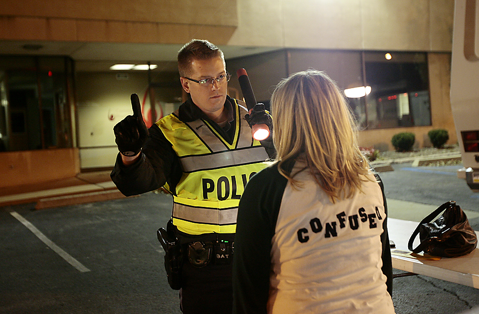 Officer Matt Phelps (left) checks the eyes of a driver suspected of being under the influence.  The Kansas City Police Department and Jackson County Sheriffs office conducted a DUI checkpoint in Kansas City.