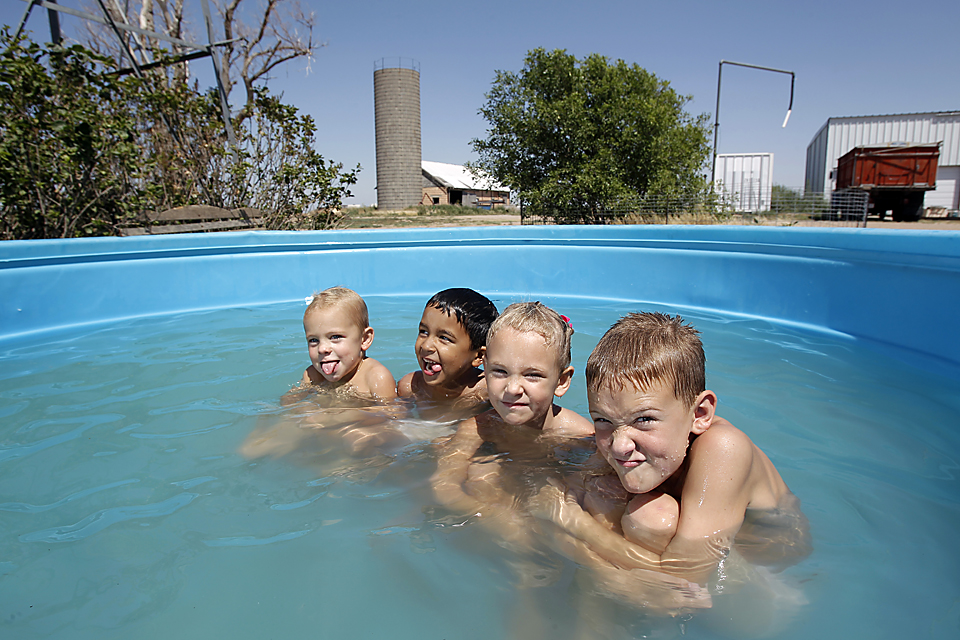 The Fink grandchildren kept cool by playing in a stock tank at Lee and Cindy Fink's Monument, Kan., family farm.