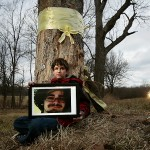 Killian Becker holds a photo of his older brother, Sebastian Becker, a 21-year-old who lost control of his car while speeding on a familiar road and died. Killian is sits near the tree his brother struck.