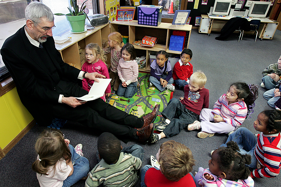 While Mark Funkhouser reads to preschoolers, Tristin Pfeifer, 4, compares his foot size with Funkhouser, the former Kansas City Mayor who is 6 foot, 8 inches tall.
