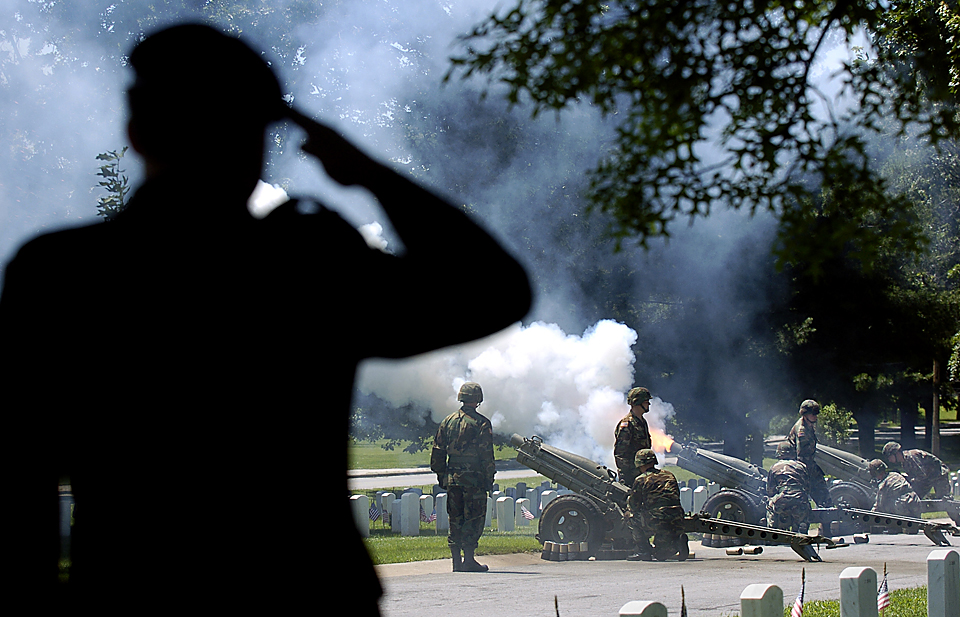 Lt. Col. Tom Tracy salutes during the Salute Battery portion of the Memorial Day Ceremony at Fort Leavenworth National Cemetery in 2004.  Capt. Anthony Lang commanded the 500th MP Detachment as they fired the 75-mm howitzers for the 21-gun salute.