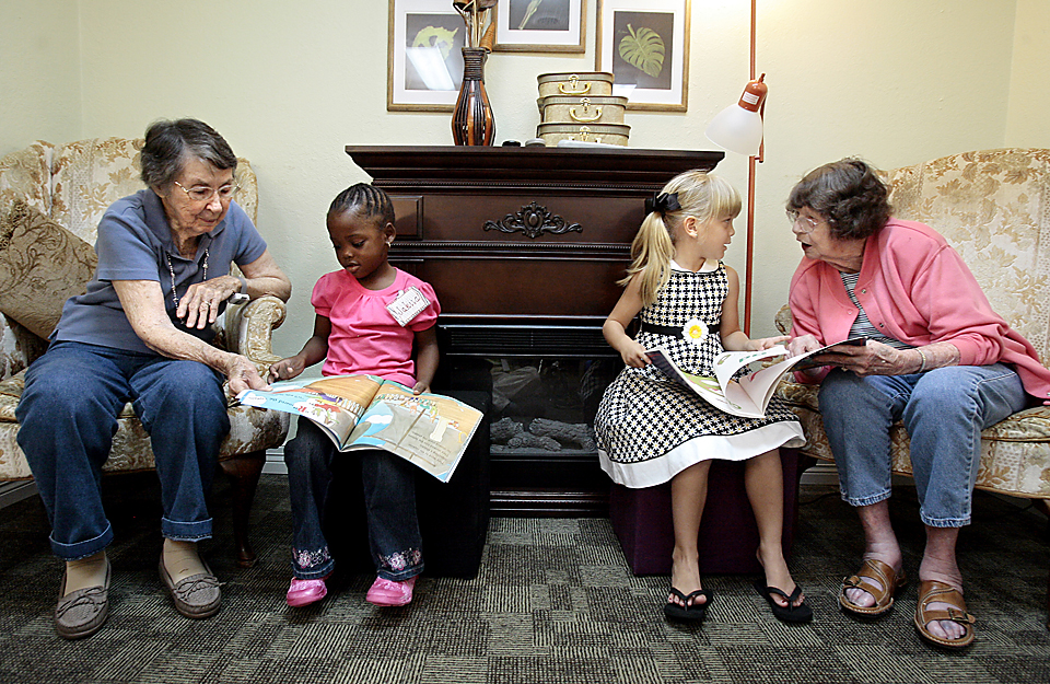 Maxine Wadkins (from left) Jakaiia Logan, Emma Gossard, and Marian Nelson read together during grandma and grandpa reading time.  Windsor Place, a Coffeyville, Kansas, nursing home, is believed to be the first in the state to welcome an entire kindergarten class into the facility for the full school year.