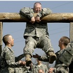 With encouragement from the rest of his Bravo Company, 40-year-old Larry Wall of Birmingham, Ala., attempts to get over the log in the low belly over exercise on the physical endurance confidence course at Ft. Leonard Wood. The Army recently raised the recruitment age from 35 to 42.
