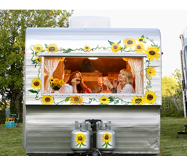 "Sisters on the Fly Elaine Toland (left) of Tecumseh, Kan., and Lori Thompson of Leawood, pose in Thompson's Kansas-themed camper.  Sisters on the Fly is a national ""sorority"" of women who meet all over the country to camp, fish, hunt and drink martinis.  Decorated campers, cowboy hats, and cigars are signatures."