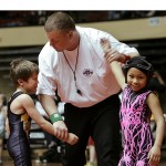 Official Jim Salker indicates the winner of a match for seventh and eighth place in the first grade, 55 pound group.  Corbin Williams of Haysville, Kan. (left) and Trinity Fields of Parsons, Kan., react at the end of the match.